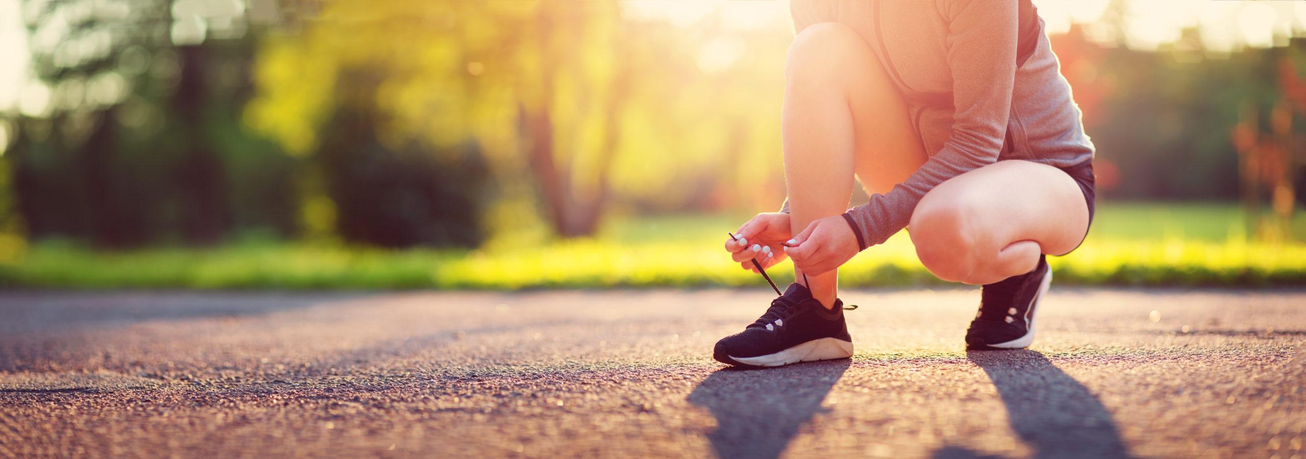 Frau bindet sich einen Laufschuh